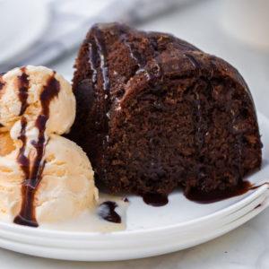 chocolate bundt cake with vanilla ice cream on white plate