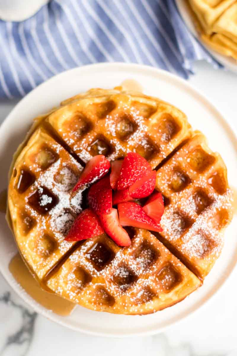 stack of waffles with syrup, powdered sugar, and strawberries