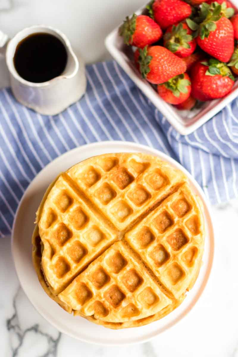 stack of buttermilk waffles with syrup cup and strawberries