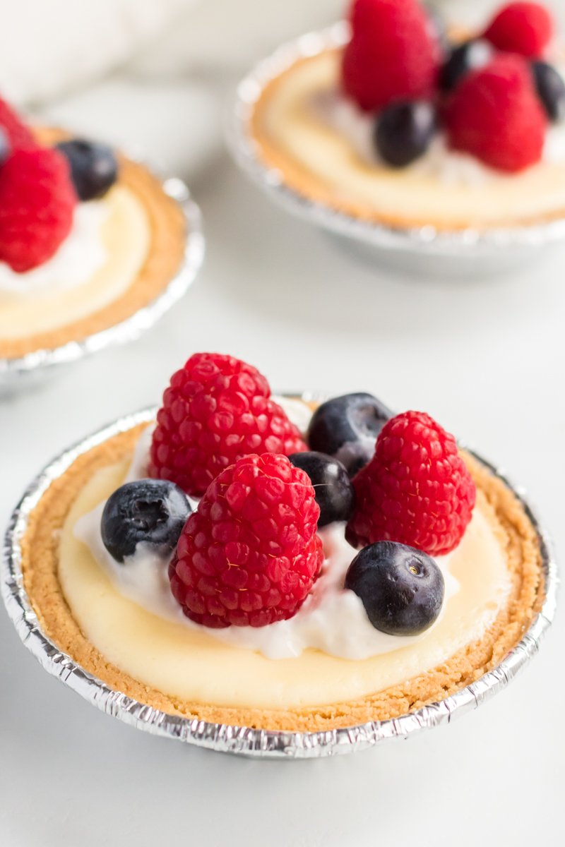 three mini cheesecake topped with raspberries & blueberries