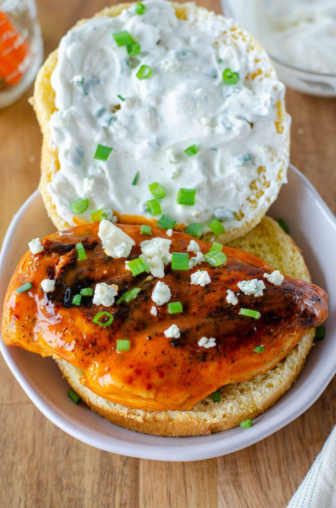 opened face buffalo chicken sandwich topped with bleu cheese crumbles