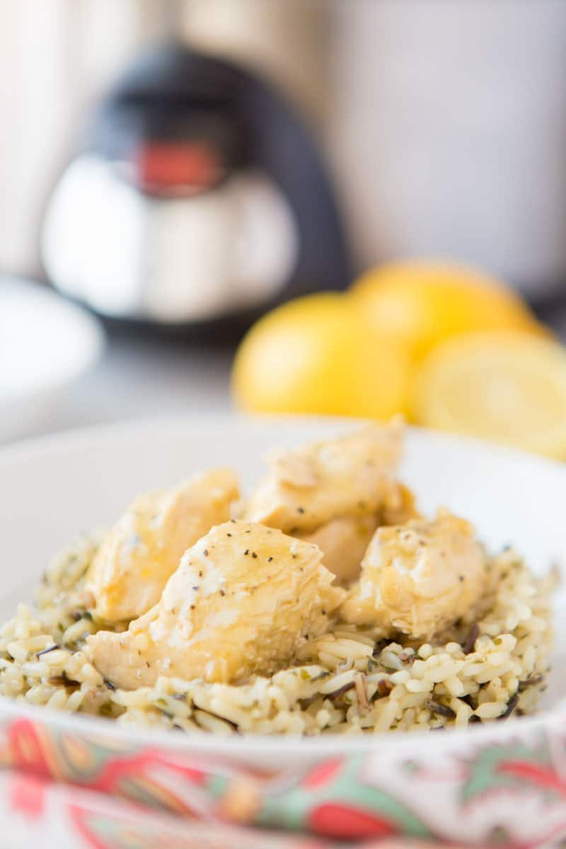 lemon chicken on a bed of rice with slow cooker & lemons in background