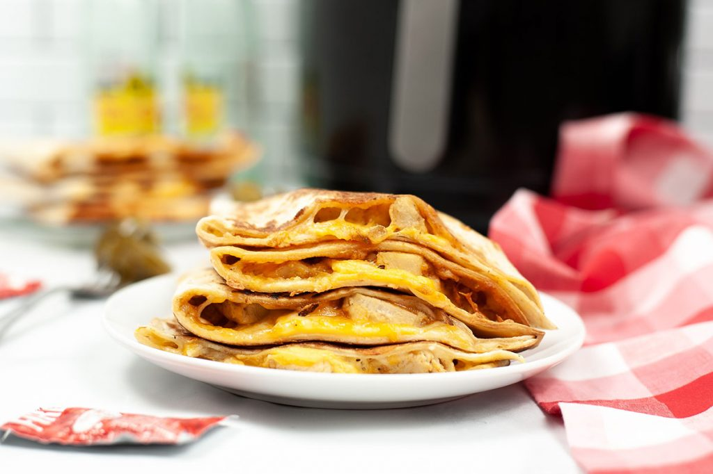 side view of a stack of quesadillas on a white plate