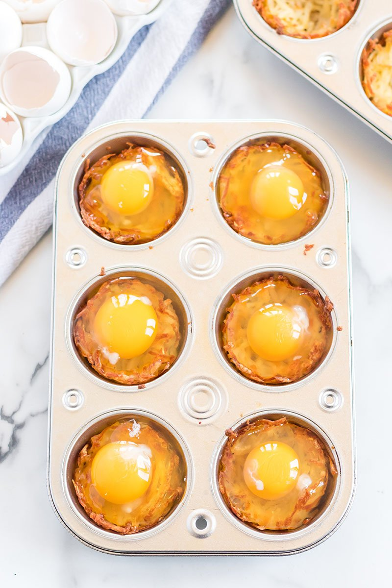 eggs cracked into hash brown cups in a muffin tin