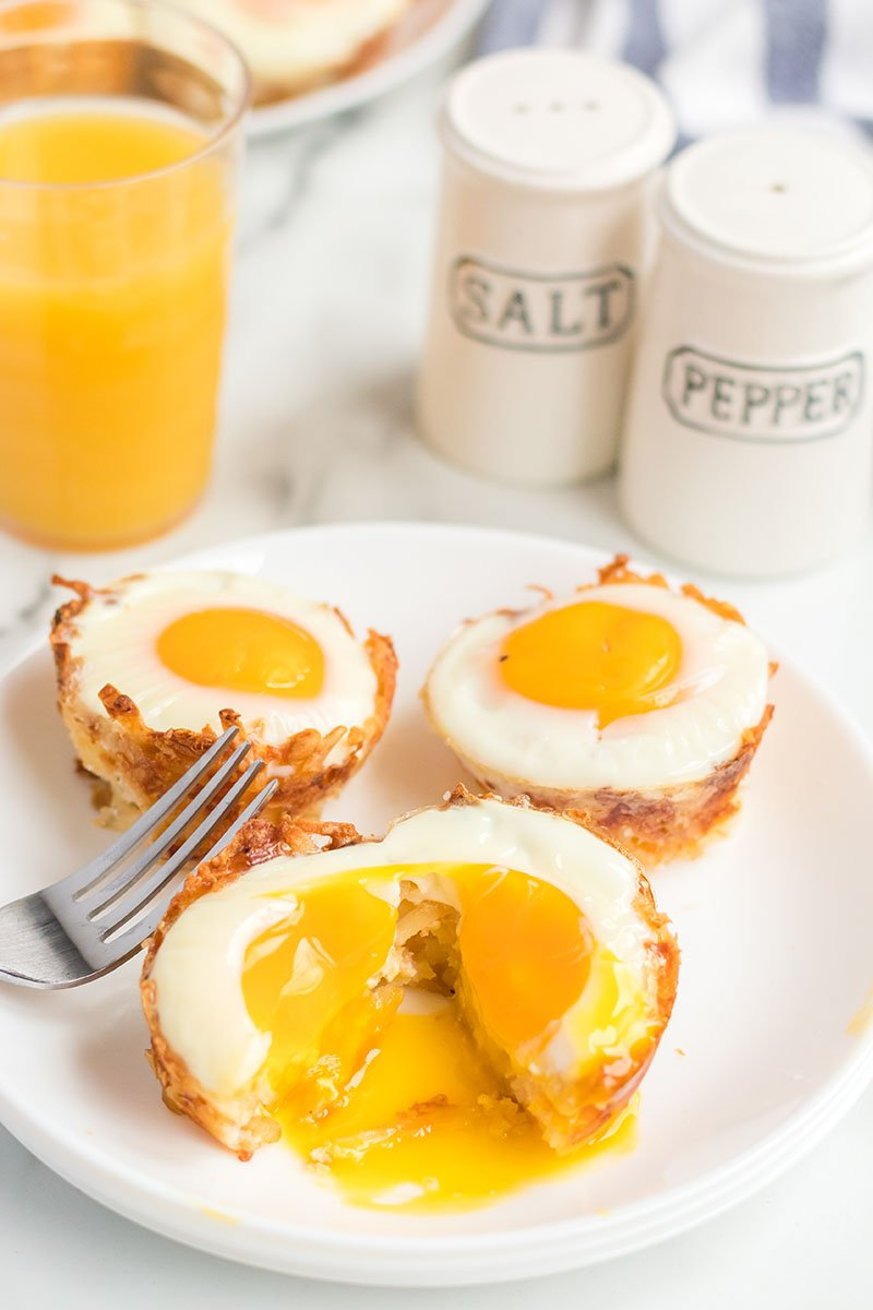 plate of egg in hash brown cups with cracked yolk spilling out