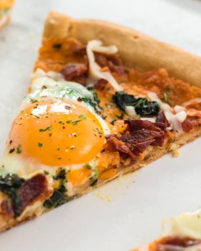 slice of bacon & spinach breakfast pizza with egg yolk