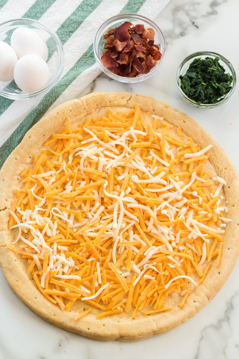 pizza crust covered in shredded cheese