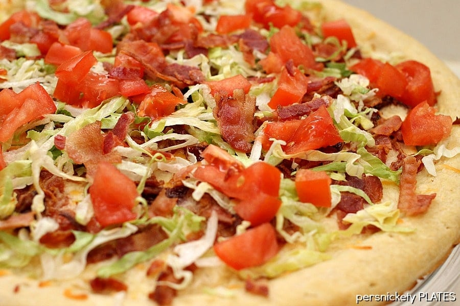 close up of blt pizza with fresh lettuce & tomatoes on top