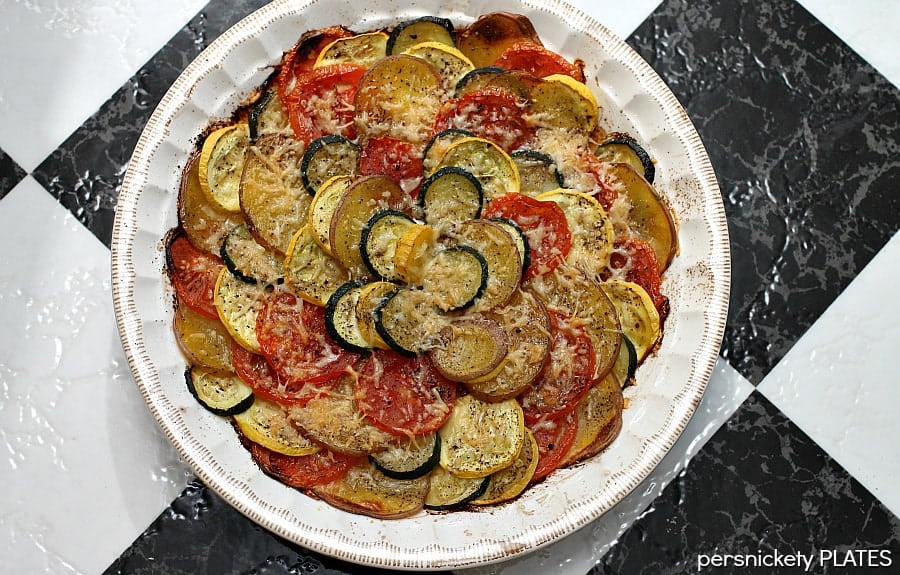 Vegetable Tian is a delicious vegetarian dish made with zucchini, squash, tomatoes, and red skin potatoes, baked together and sprinkled with cheese. This colorful vegetable recipe makes a beautiful side dish or a main vegetarian meal.