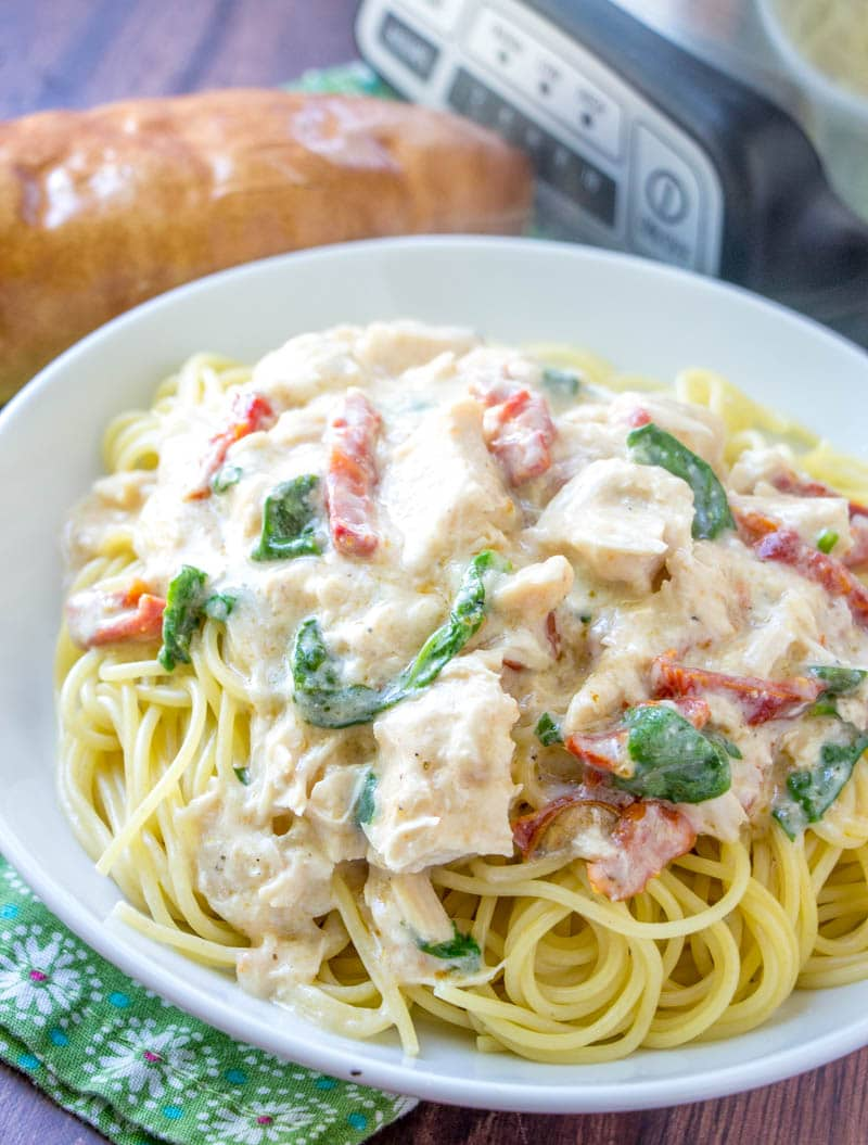 white bowl filled with spaghetti noodles topped with chicken alfredo