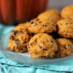 clear plate of pumpkin chocolate chip cookies on a teal napkin with a pumpkin in the backgroud