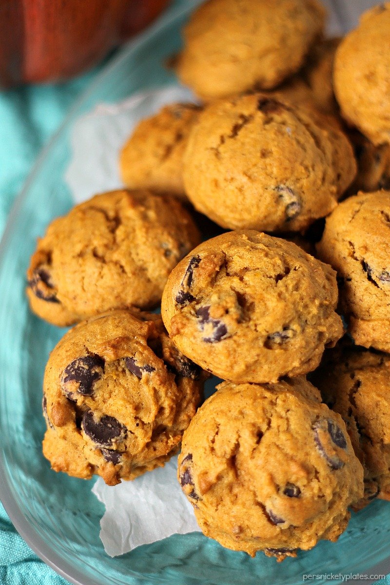 horizontal platter of pumpkin chocolate chip cookies on clear plate with a teal napkin