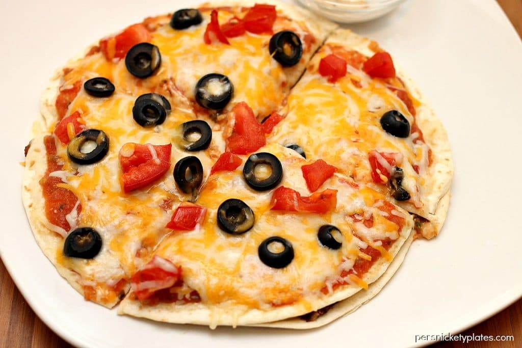 mexican pizza topped with black olives on a white plate