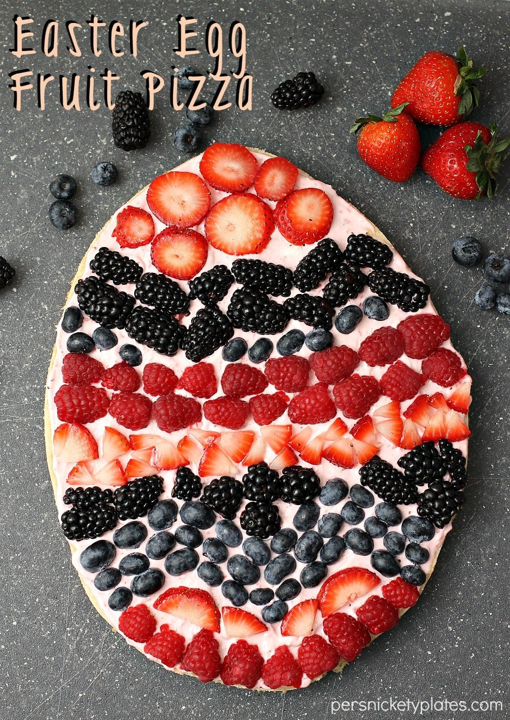 A sugar cookie base with a strawberry cream cheese frosting topped with fresh berries makes the perfect Easter Egg Fruit Pizza. Fun to decorate with the kids! | www.persnicketyplates.com