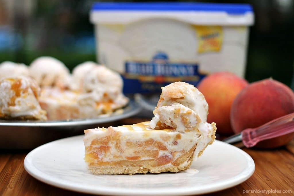 Super simple Peaches and Cream Ice Cream Pie is filled with broiled peaches, creamy vanilla bean ice cream, in a graham cracker crust and drizzled with butterscotch sauce. The perfect dessert for a hot summer day! | Persnickety Plates #SunsOutSpoonsOut #ad