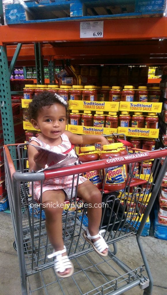 girl in costco shopping cart buying ragu sauce