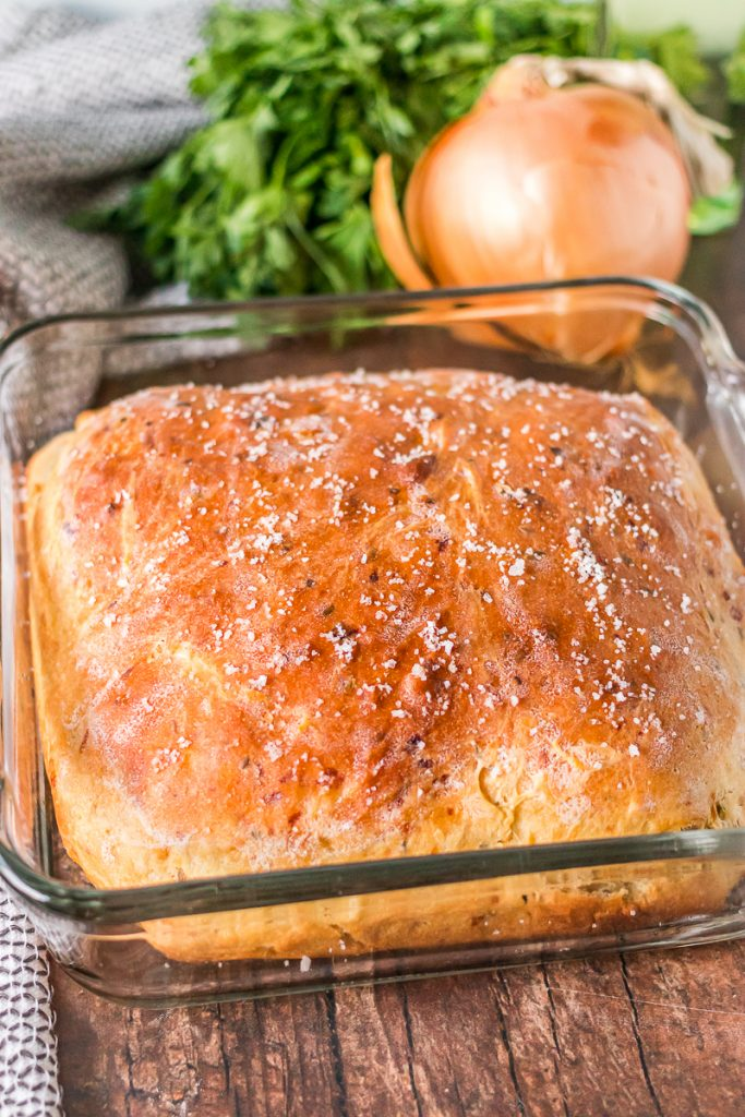 loaf of onion dill bread in baking dish