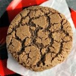 closeup of single chocolate crinkle cookie on buffalo plaid plate