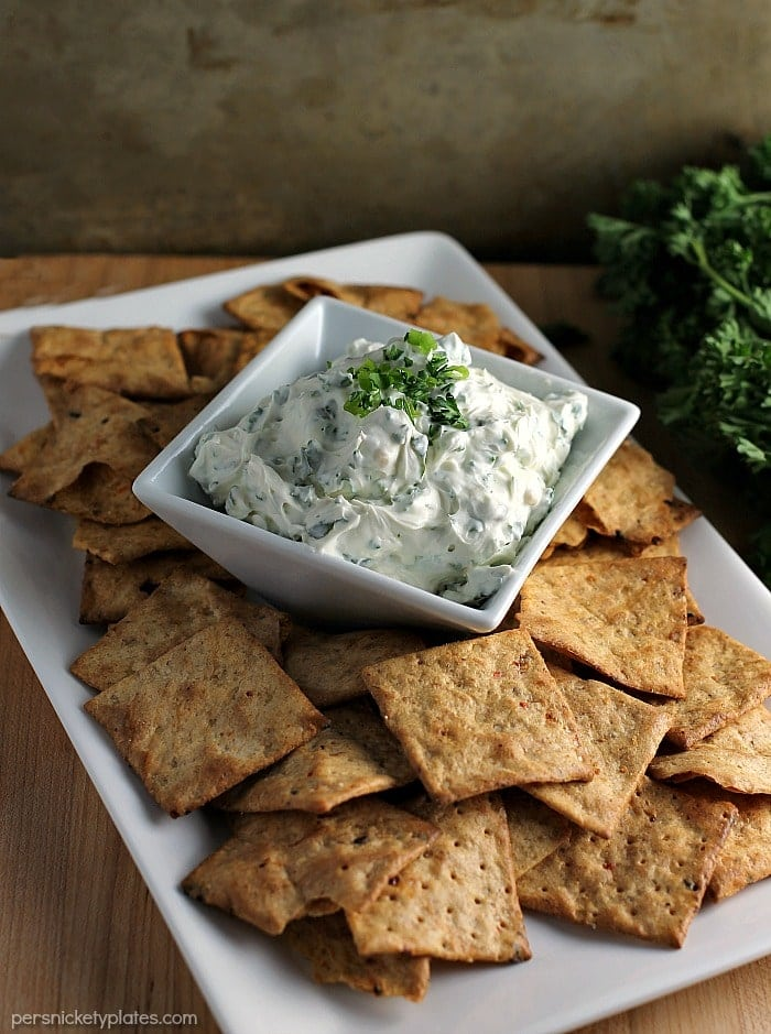 garlic herb dip surrounded by chips on white platter