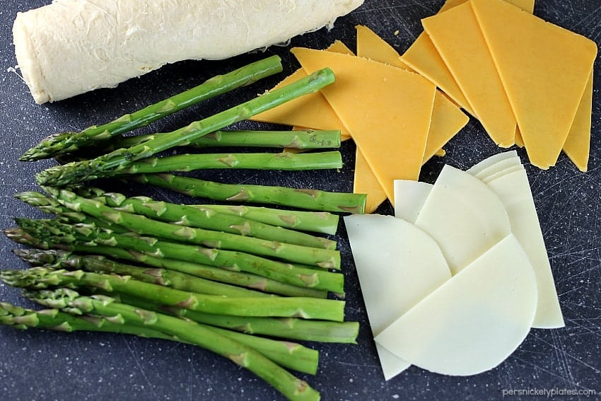 fresh asparagus laid out with sliced cheese for asparagus puffs