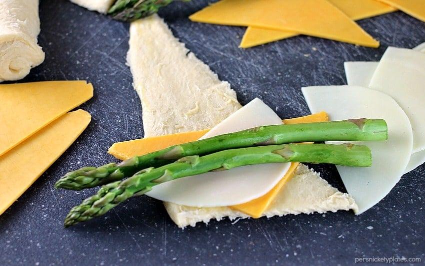 cheesy asparagus puffs prepped on a cutting board