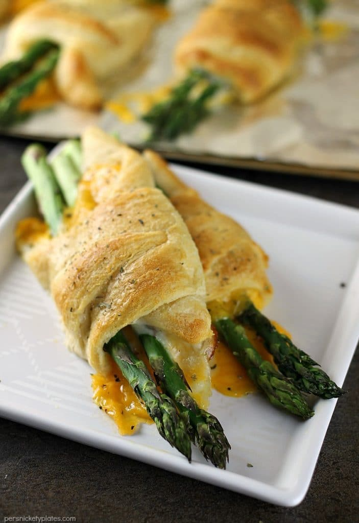 two cheesy asparagus puffs on a white plate
