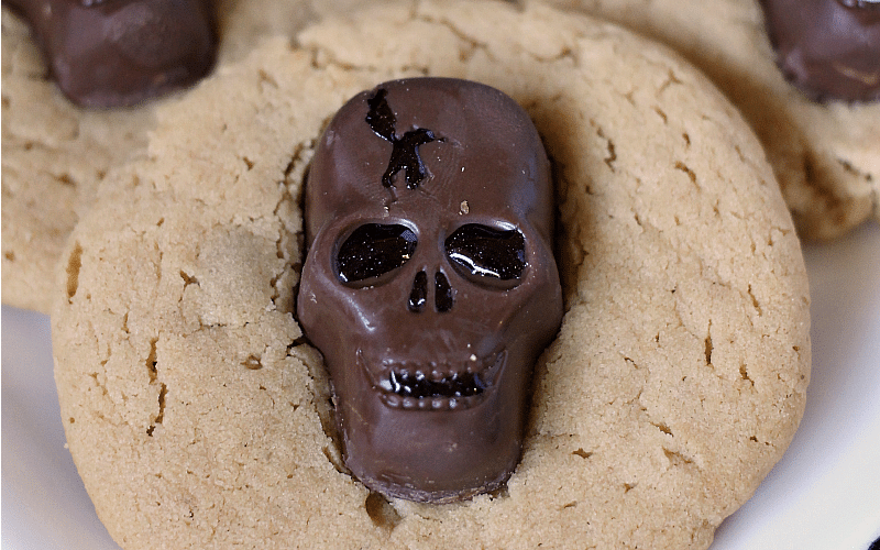 Peanut Butter Butterfinger Skull Cookies start with a soft and chewy from scratch peanut butter cookie then are topped with a spooky, decorated Butterfinger Peanut Butter Skull Cup. Perfect for any Halloween party!   www.persnicketyplates.com