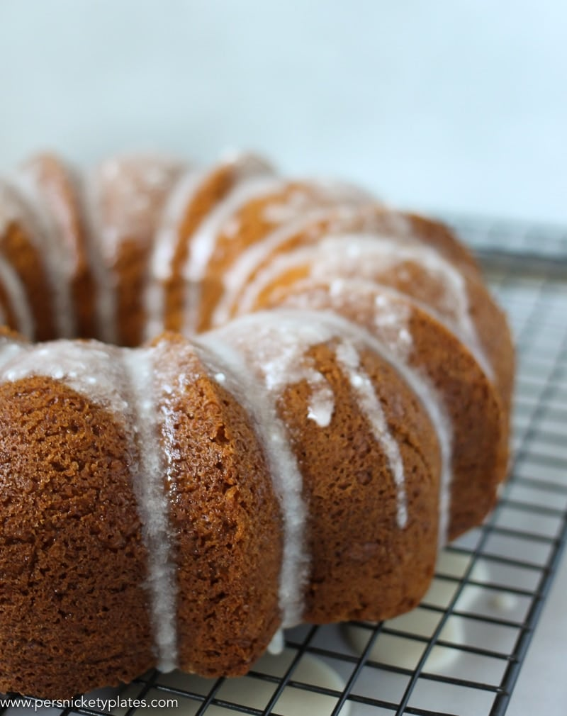 angled shot of butterscotch bundt cake with powdered sugar glaze on cooling rack