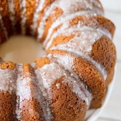 angled shot of butterscotch bundt cake with powdered sugar glaze