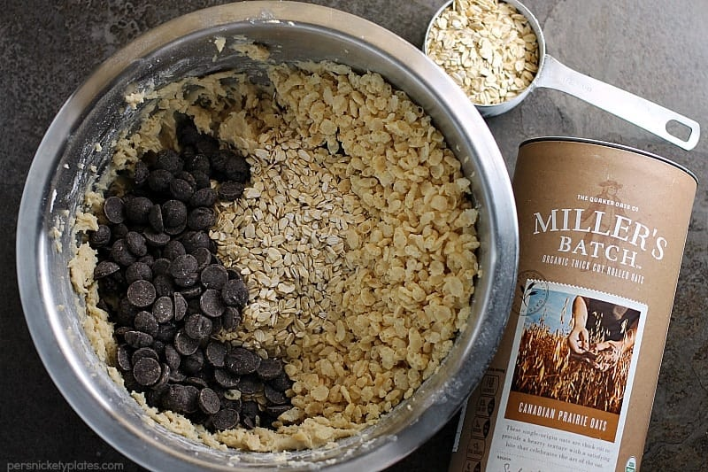 mixing bowl filled with chocolate chips, miller's batch oats, crispy rice and a measuring cup with oats