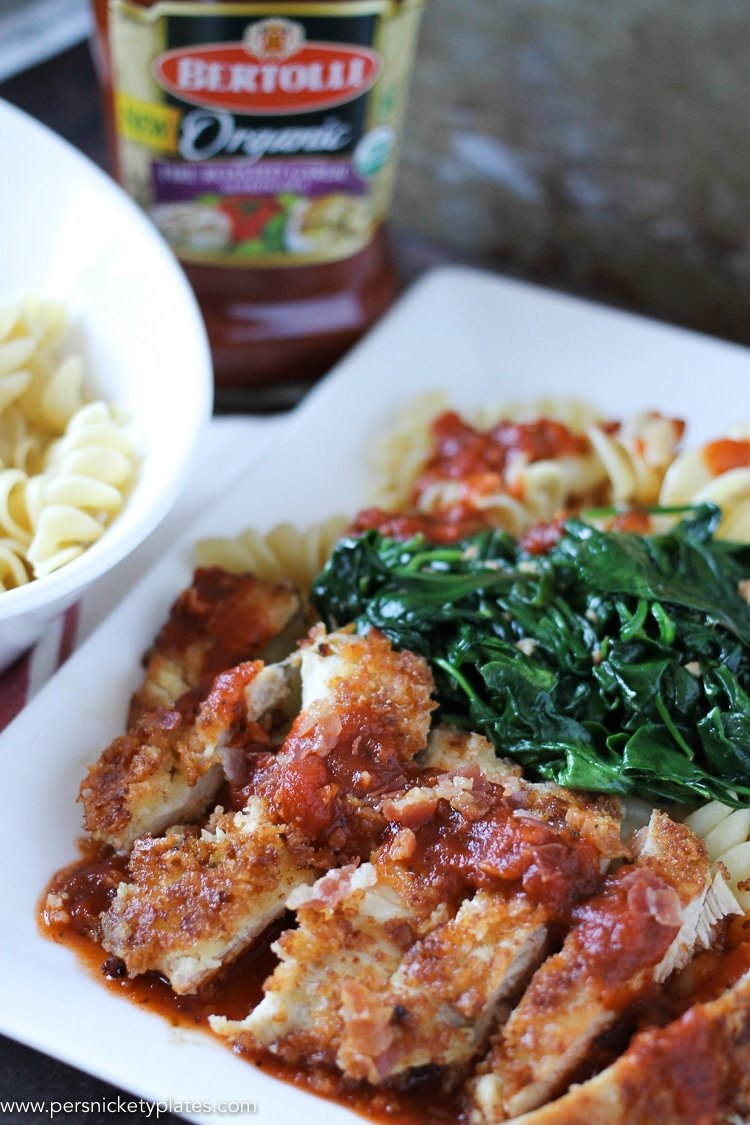 chicken florentine on a white plate with pasta and jarred marinara in the background