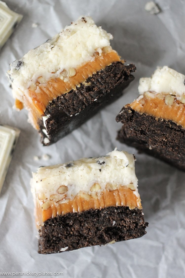 three cookies and cream caramel layer bars on parchment paper