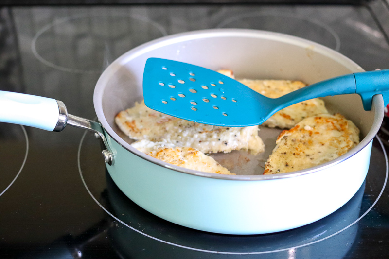 skillet with chicken breasts on stove with spatula