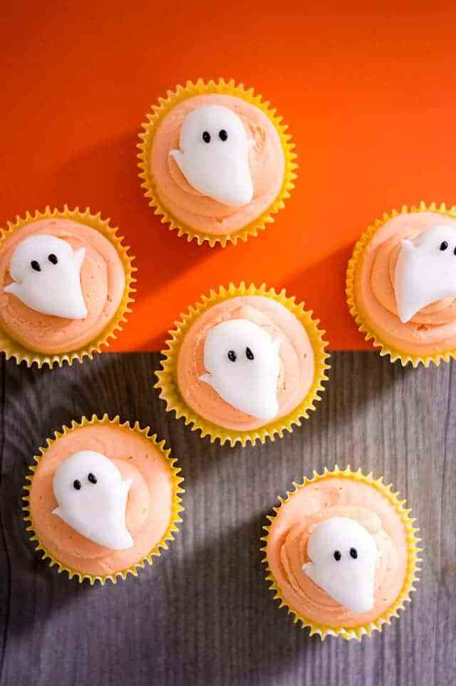 overhead shot of orange frosted cupcakes with ghosts on top