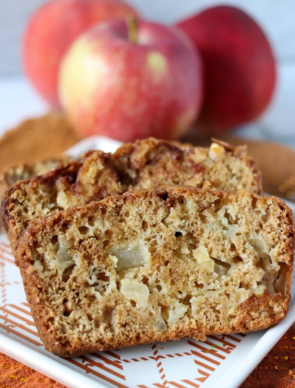 apple bread sliced on plate with apples in background