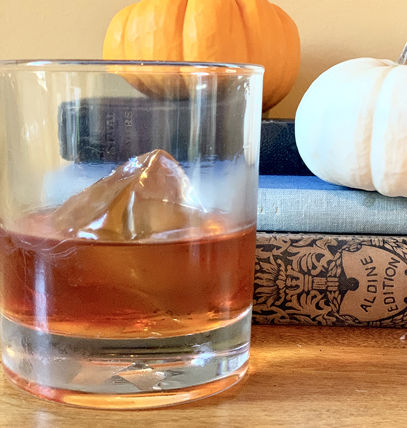 single glass of bourbon cocktail with pumpkins in background