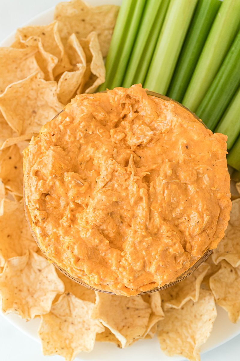 overhead shot of buffalo chicken dip on a platter with chips & celery