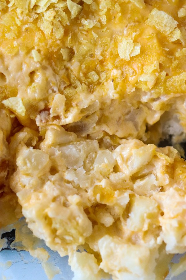 close up of cheesy potato casserole topped with chips