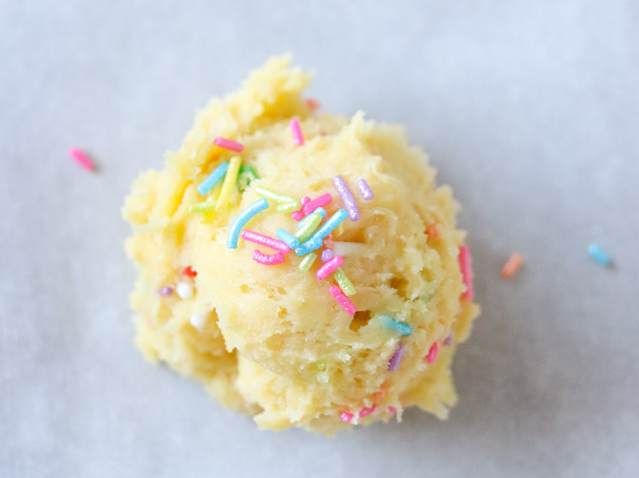 close up of cookie dough ball with rainbow sprinkles