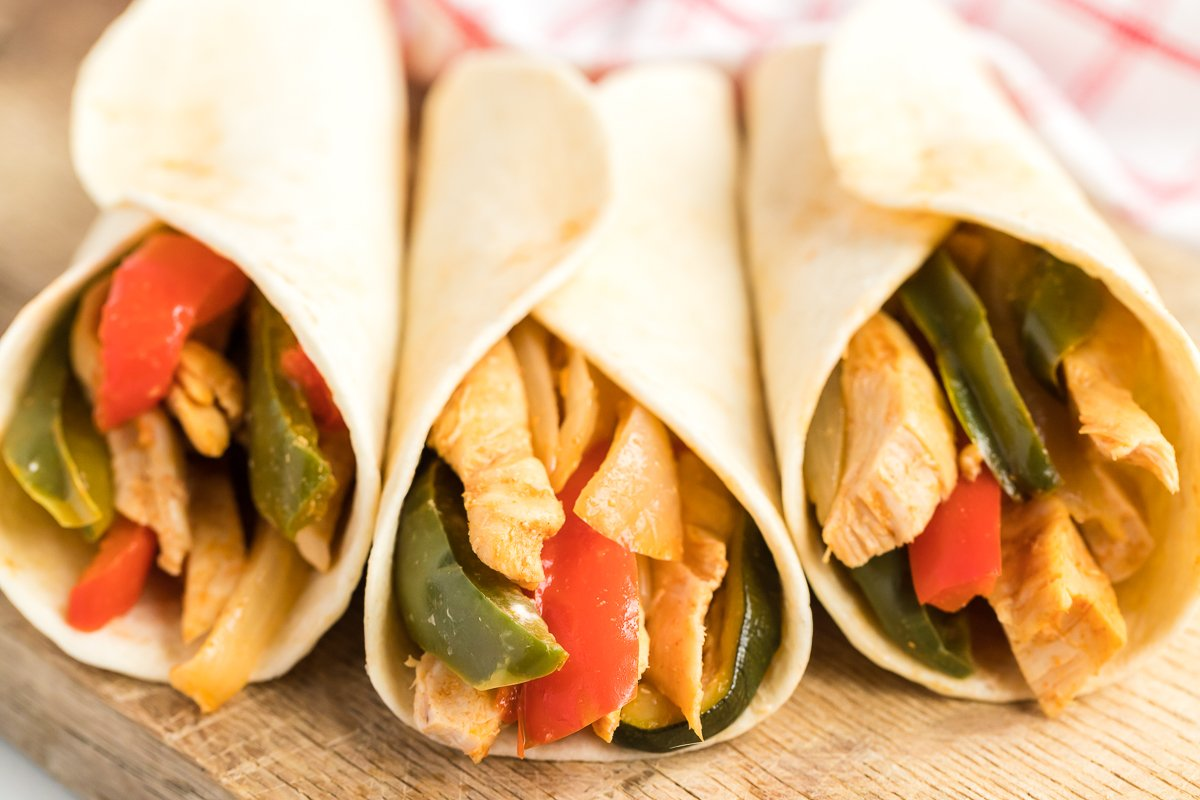 three chicken fajitas in tortillas