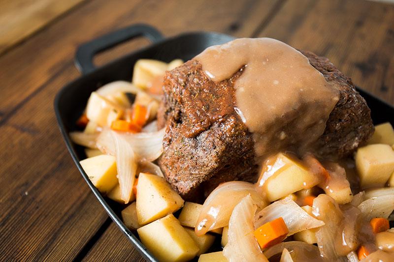 platter of pot roast topped in gravy