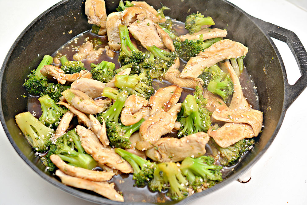 skillet of chicken and broccoli topped with sesame seeds
