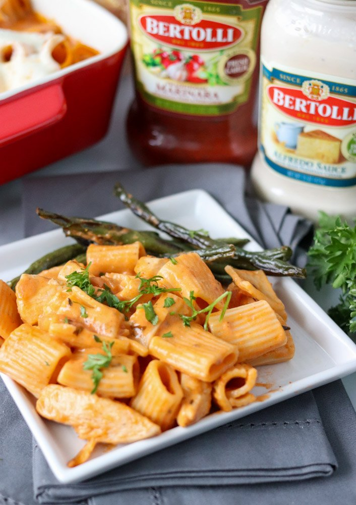 rosa pasta on a white plate with green beans