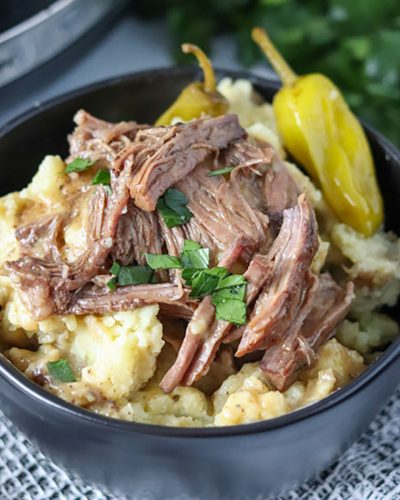 close up on bowl of mississippi pot roast over mashed potatoes