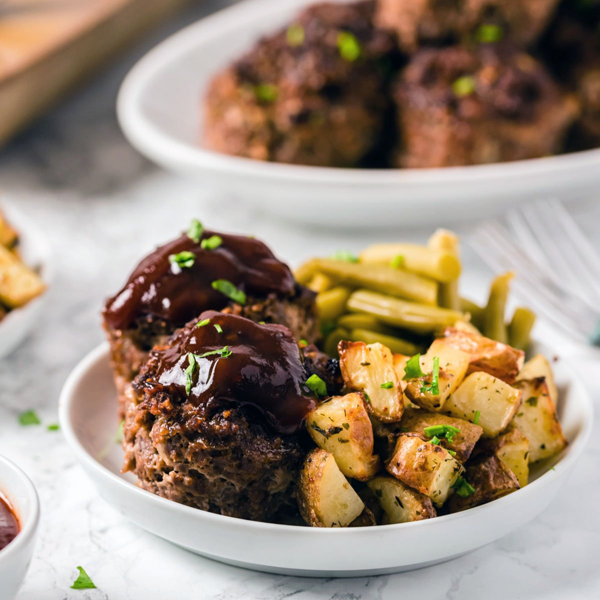 plate of meatloaf muffins, roasted potatoes, and green beans