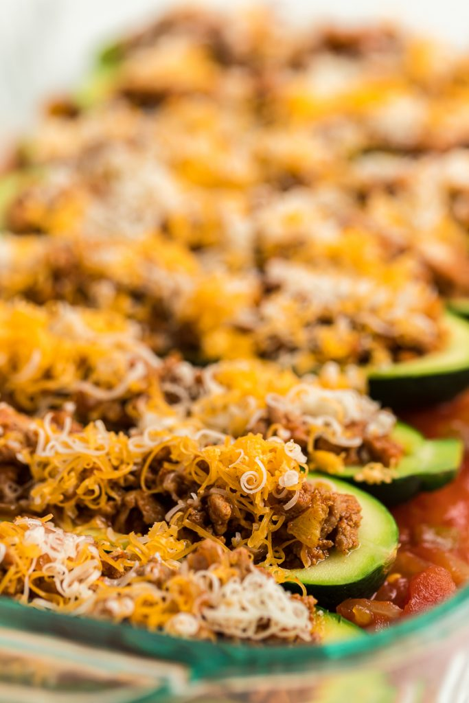 zucchini boats with shredded cheese in pan reay for baking