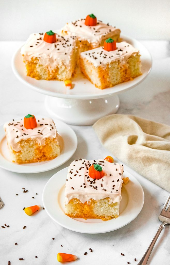 halloween poke cake on a white plate in front of platter of cake slices
