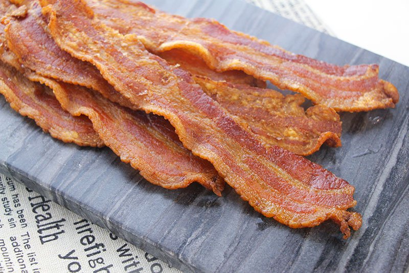stack of crispy bacon on a grey plate
