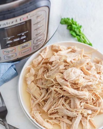 plate of shredded chicken breasts next to an instant pot