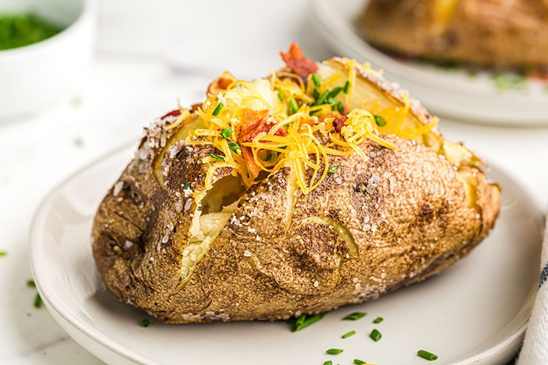 loaded baked potato topped with cheese & bacon & chives